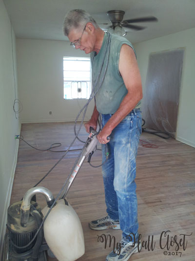 My man sanding the wood floor
