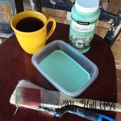 Paint, brushes, container and a cup of coffee