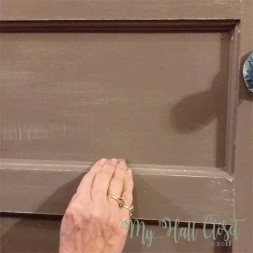Use sand paper or a sanding block to distress the door