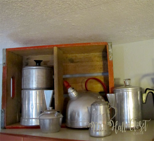 Collection of aluminum pots on top with coke box